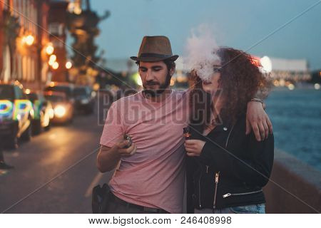 Loving Couple Of Hipsters On Date. Guy In Hat And T-shirt Is Holding Electronic Cigarette And Huggin