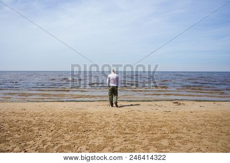 A Man In A T-shirt And Trousers Walks By The Baltic Sea. The Guy Goes To The Sea, To The Horizon, Ad