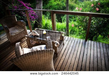 beach bungalow terrace with cosy wooden chairs surrounded by jungle vegetation - relaxing holiday home