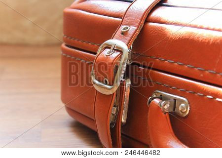 Old leather suitcase on the floor. Brown suitcase. Summer is coming soon. Summer vacation and travel. Vintage accessories for business. Travel bag for summer vacation. The baggage for the trip. Lifestyle. Waiting for the trip