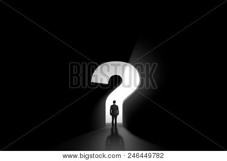 businessman standing in front of a portal shaped as a questionmark