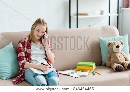Teen Student Girl Doing Homework On Couch And Talking By Phone