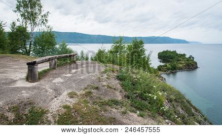 Shamanka, Shamans Rock On Baikal Sea Near Slyudyanka, Russia. Wooden Bench On Shore Of Lake