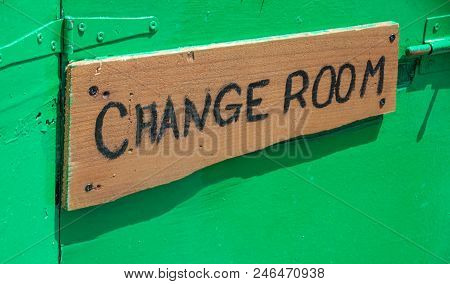 Wooden Signage Outside The Room. Apparel Changing Notice Board Hanging In The Wall. Fitting Clothes