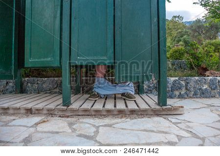 A Wooden Architecture Painted With Dark Green. The Half Way Door Room Sitting Above The Tiled Pathwa