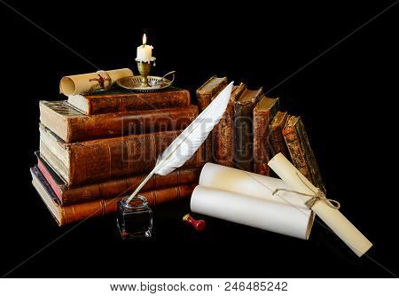 Many old books, rolls of manuscripts, white goose quill, inkwell and a burning candle in a copper candlestick isolated on a black background poster