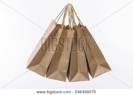 Group Of Three Hanging Brown Paper Bags For The Shop. White Background.