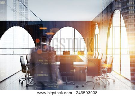 Businessman In A Modern Office Meeting Room Interior With A Concrete Floor, Arched Wooden Walls And