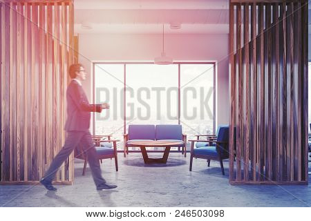Businessman Walking In Loft Office Waiting Room Interior With A Blue Couch And Armchairs Near A Coff