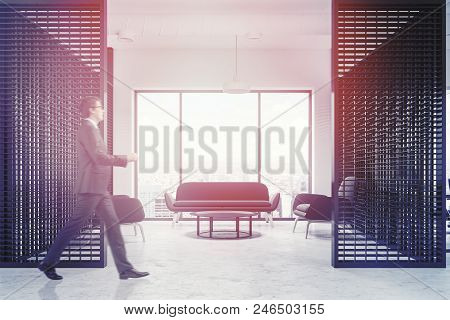 Loft Windows Office Waiting Room With Black Couch And Armchairs Near A Coffee Table Standing On A Co