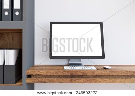 Mock Up Computer Screen Standing On A Wooden Table In A Room With White Walls And A Bookcase. 3d Ren