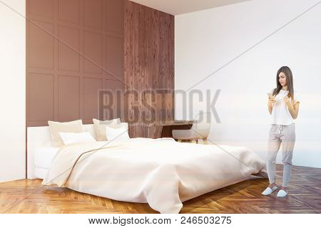 Woman With A Smartphone In A White And Gray Wall Bedroom Corner With A White Bed, A Table With Compu