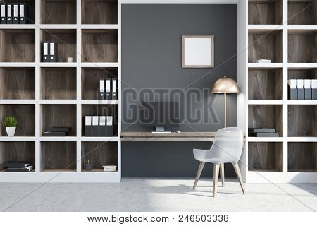 Gray Home Office Interior With A Concrete Floor, A Computer Table And Bookcases With Folders. Concep