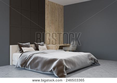 Dark Gray And Wooden Bedroom Interior With A Concrete Floor, A Double Bed And A Home Office Corner.