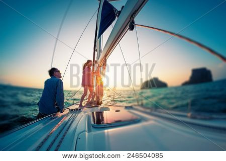 Couple works with ropes on the sail boat at sunset. Tilt shift effect applied