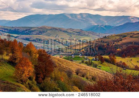 Small Village On Hills In Autumn. Lovely Countryside Of Carpathian Mountains. Mighty Ridge In The Di