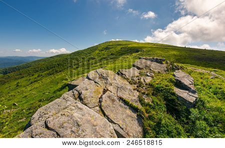 Mountain Landscape With Stones Laying Among The Grass On Top Of The Hill Side Under The Cloudy Summe