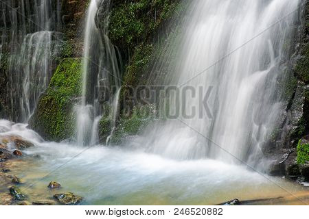 Close Up Of Waterfall Foot With Mossy Rock. Beautiful Calm Nature Background. Freshness And Power Of