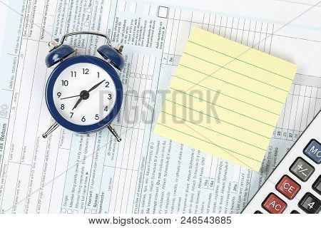 Alarm Clock, Blank Yellow Note And Calculator On 1040 Tax Form