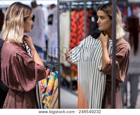 Beautiful Girl Trying Dress Near Mirror - Shopping, Fashion, Style And People Consumer Concept