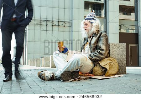 Starving man. Poor starving street man wearing tattered old clothes sitting outside the office center asking for help poster