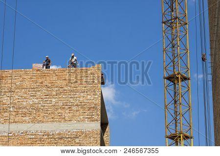 Building brick block wall on construction. Construction mason worker bricklayer making a brickwork poster