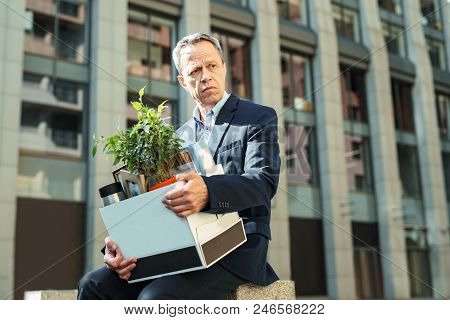 Personal Box. Elderly Wrinkled Experienced Office Manager Holding His Personal Box While Going Home
