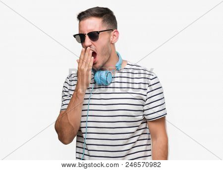Handsome young man wearing headphones bored yawning tired covering mouth with hand. Restless and sleepiness.