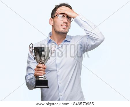 Handsome young man holding trophy stressed with hand on head, shocked with shame and surprise face, angry and frustrated. Fear and upset for mistake.