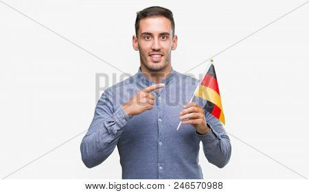 Handsome young man holding a flag of Germany very happy pointing with hand and finger