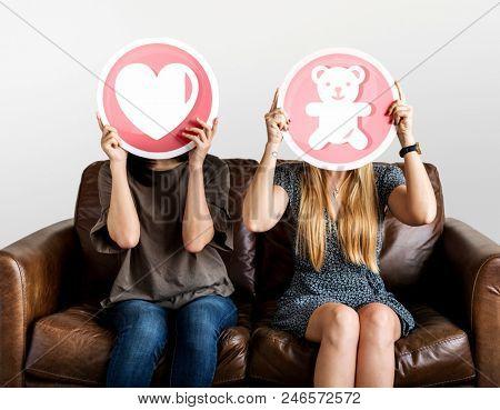 Women holding up valentine icons