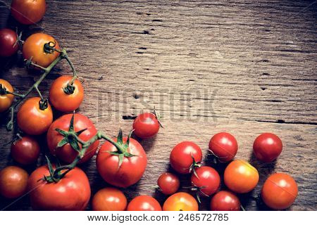 Closeup of fresh organic tomatoes on wooden background
