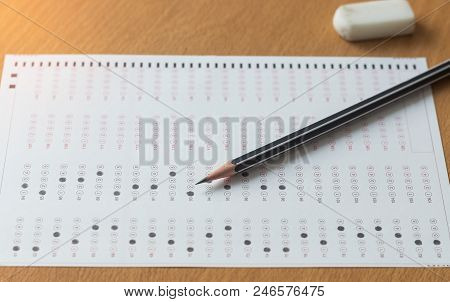 Black Pencil On Paper Computer Sheet And Eraser On Table.  Standardized Test Form With Answers Bubbl