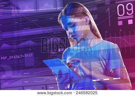 Careful Student. Serious Young Student Standing In Front Of A Transparent Screen And Looking Attenti
