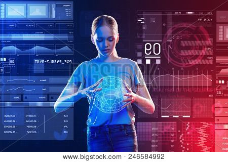 3d Earth Image. Calm Attentive Young Girl Looking Attentively At The Hologram Of The Earth While Hol