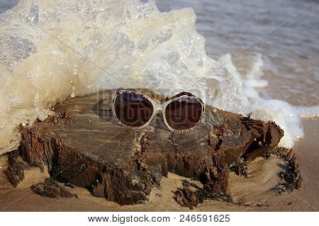 Sunglasses On A Wooden Stump On The Sea Beach. View Of Stump With Sunglasses And Sea Wave.