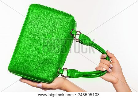 Beautiful Female Hands With Manicure Hold An Green Handbag.