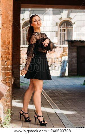 the girl is posing smiles. Emotional portrait of Fashion stylish portrait of pretty young woman. city portrait. brunette in a black dress with stars and planets on a dress. expectation. dreams poster