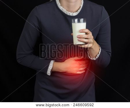The Girl Holds Onto Her Stomach And Holds A Glass Of Milk, A Black Background, Pain And Heartburn In