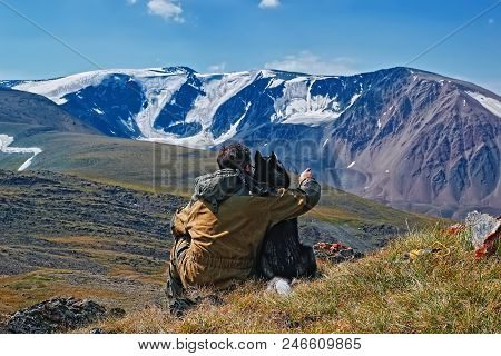 Concept Of Traveling With Dog In The Mountains. Man With Siberian Husky Looks At The Snow-capped Mou