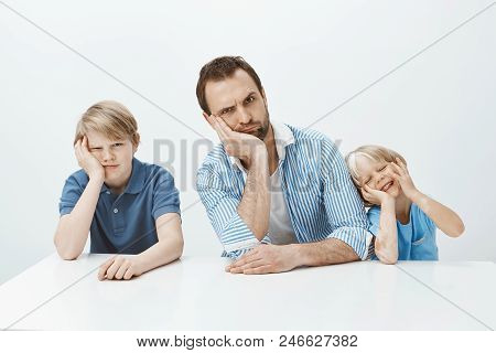 Portrait Of Funny Family Of Father And Sons Sitting At Table, Leaning Head On Hand And Making Faces