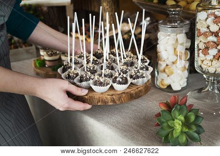 Chef putting wooden tray with chocolate cookie ball pops on sticks on candy bar table poster