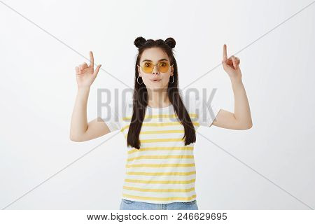Impressed Excited Joyful Female In Stylish Outfit And Yellow Glasses, Folding Lips, Saying Wow, Poin