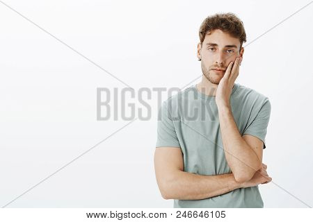 How Boring, Leave Me Alone. Portrait Of Careless Handsome Guy In Earrings, Holding Hand On Palms And