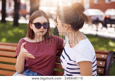 Beautiful Two Young Women In Trendy Shades, Discuss Something, Talk With Gestures, Sit On Bench Outs