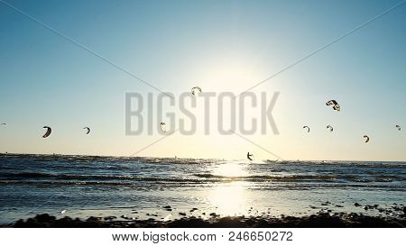 Kitesurfing In The Summer At Sea In Windy Weather At Sunset, Extreme Rest. Camera Movement Along The
