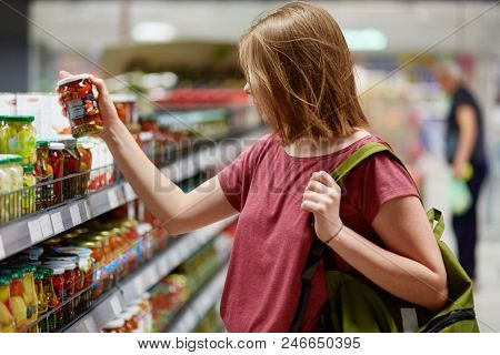 Sideways Shot Of Pretty Young Femake Customer Holds Canned Goods In Glass Container, Stands In Food