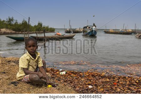 Cacheu, Republic Of Guinea-bissau - February 1, 2018: Young Boy Playing Next To The Water In The Por