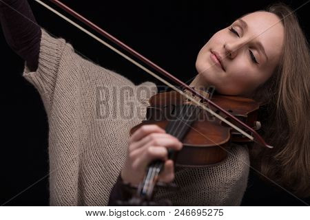 young woman with half of her hair shaved while playing a baroque violin on a black background poster