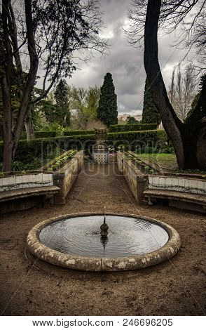 Small round fountain in a garden in a winter day with overcast sky